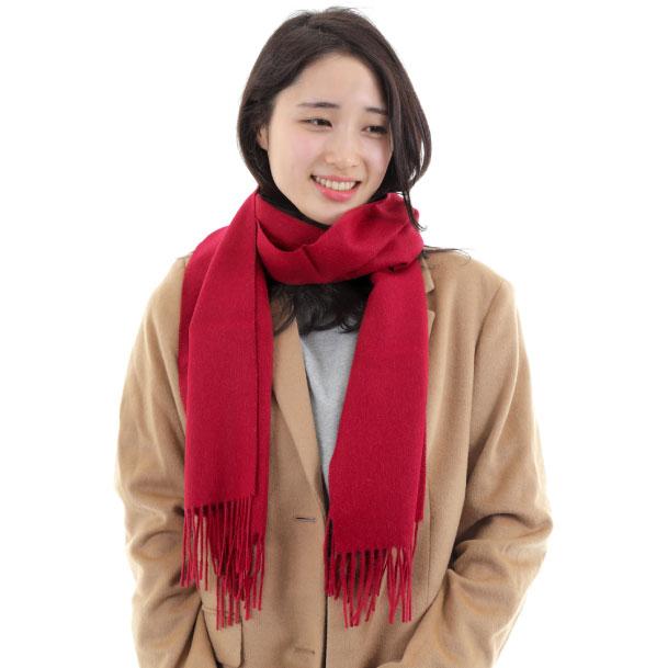 暖かいアルパカニットのマフラーをしているため、幸せそうな表情をしている女性